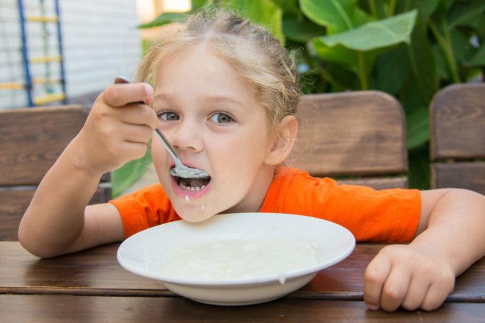 Девочка ест молочную кашу