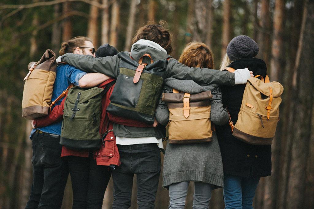 Молодые люди стоят в лесу в обнимку спиной к объективу с рюкзаками на плечах