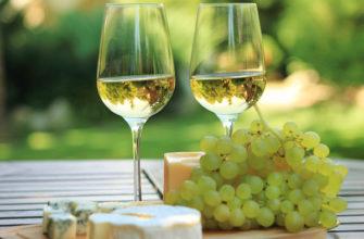 Бокалы с белым вином и виноградная гроздь на столе